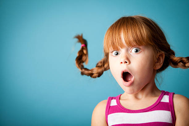 red-haired girl with upward braids and look of surprise - astonishment stock photos and pictures