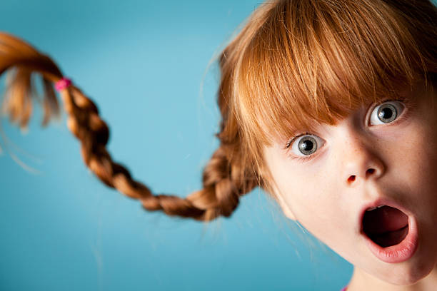 Red-Haired Girl with Upward Braids and Look of Surprise Color photo of a silly, red-haired girl with upward braids and a look of surprise! gasping stock pictures, royalty-free photos & images