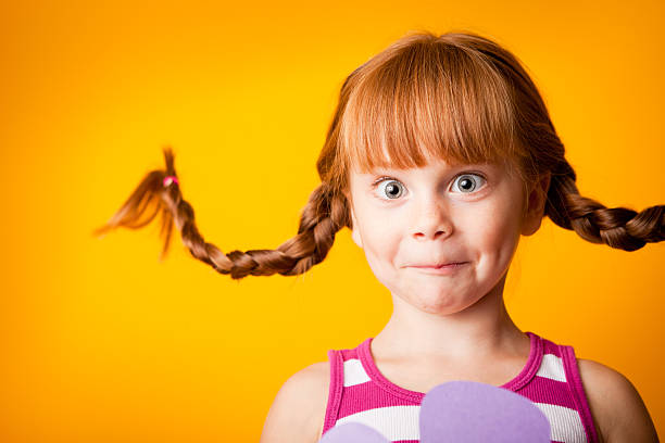 Red-Haired Girl with Upward Braids and Silly Face stock photo