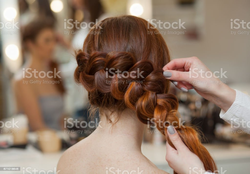 red-haired hairy girl, hairdresser weaves a French braid stock photo