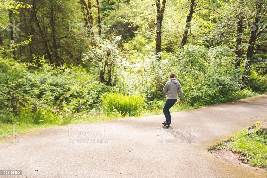 Red-haired male skateboards through forest stock photo