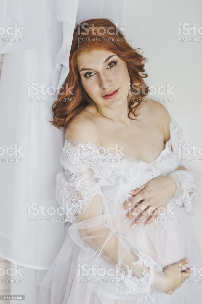 Red-haired pregnant girl in a white robe 6851. photo libre de droits