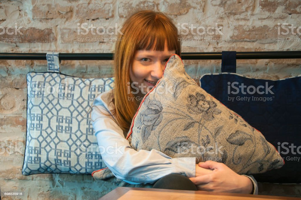 Red-haired smiling and hiding behind a pillow young European girl in a cafe on a brick wall background. stock photo