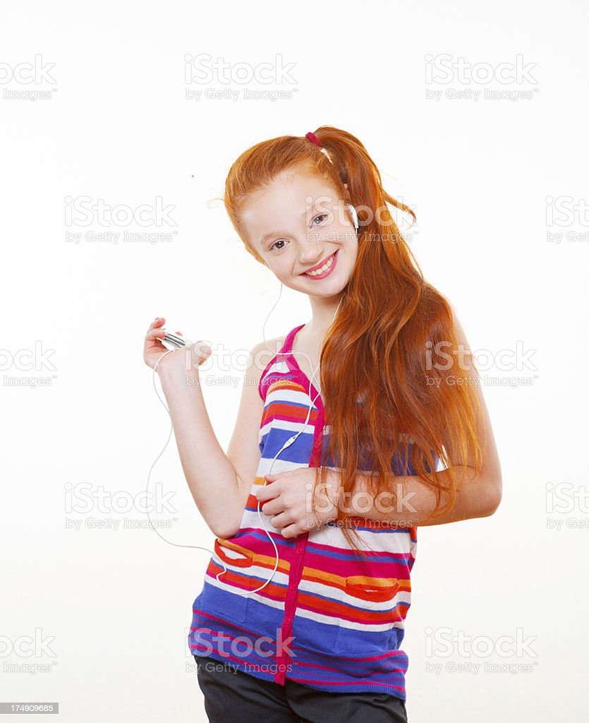 Red-haired teenage girl enjoying listeing to music royalty-free stock photo