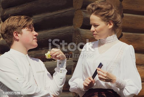 istock A red-haired village boy and beautiful girl dressed in the style of the 19th century. Human relationships. Historical reenactment 1182027539