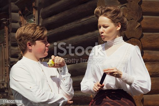istock A red-haired village boy and beautiful girl dressed in the style of the 19th century. Human relationships. Historical reenactment 1182027578