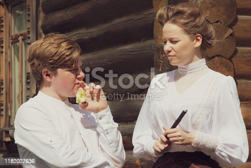 istock A red-haired village boy and beautiful girl dressed in the style of the 19th century. Human relationships. Historical reenactment 1182027636