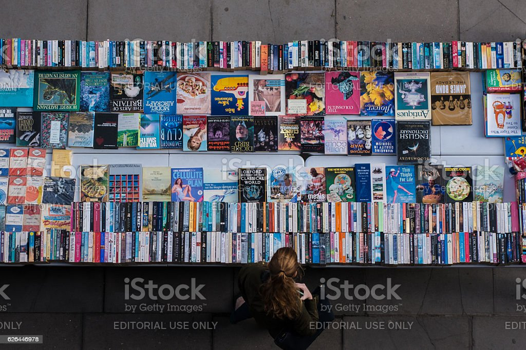 Red-haired woman browsing second-hand books at abook market. stock photo