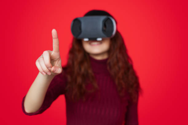 red-haired woman exploring virtual reality - vr red background imagens e fotografias de stock