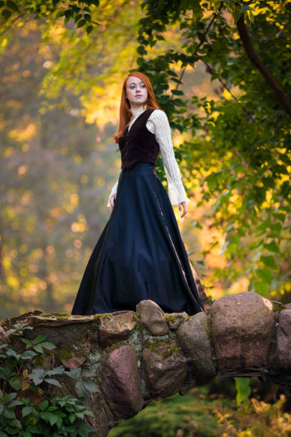 Red-haired woman in Victorian outfit with autumn park stock photo