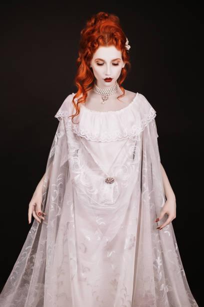 rothaarige frau im weißen kleid mit blasser haut auf schwarzem hintergrund. suchen sie frau vampir im gotischen stil in den halloween - gothic kleid stock-fotos und bilder