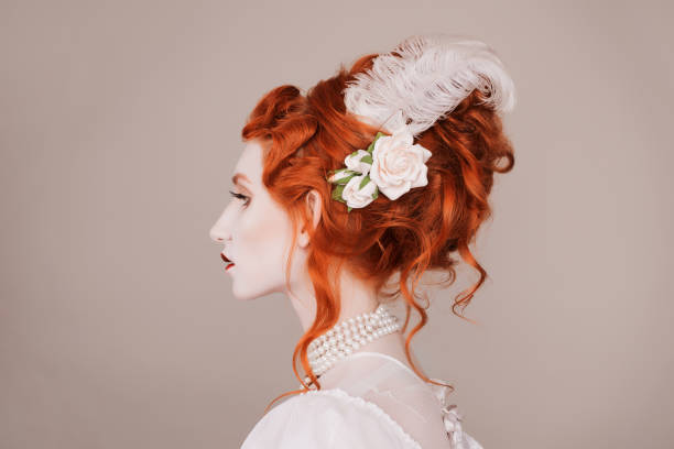 Red-haired woman in white dress with pale skin on gray background.  A vampire woman with a beautiful hairdo with a feather and flowers in her hair stock photo