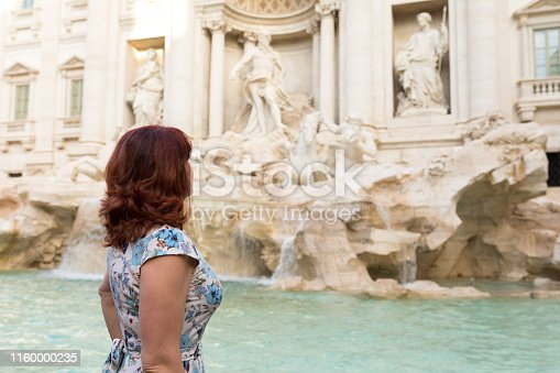 A red-haired woman is looking at the majestic Trevi Fountain in Rome on a sunny autumn day. The woman turned sideways looks inspired and is wearing a colorful beautiful dress.