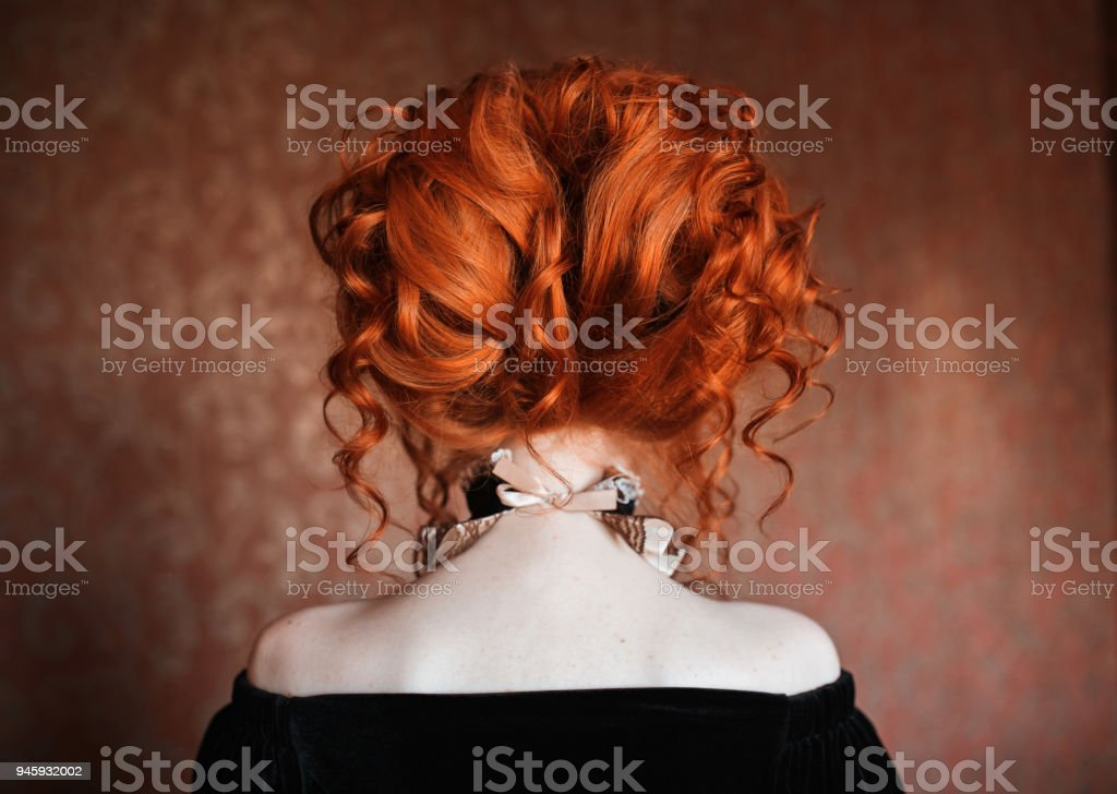 Red-haired woman with beautiful hairstyle standing back. stock photo