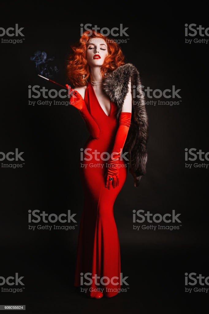 58a67debd4607b Roodharige vrouw met krullend haar in de rode jurk en lange handschoenen  rook op zwarte achtergrond