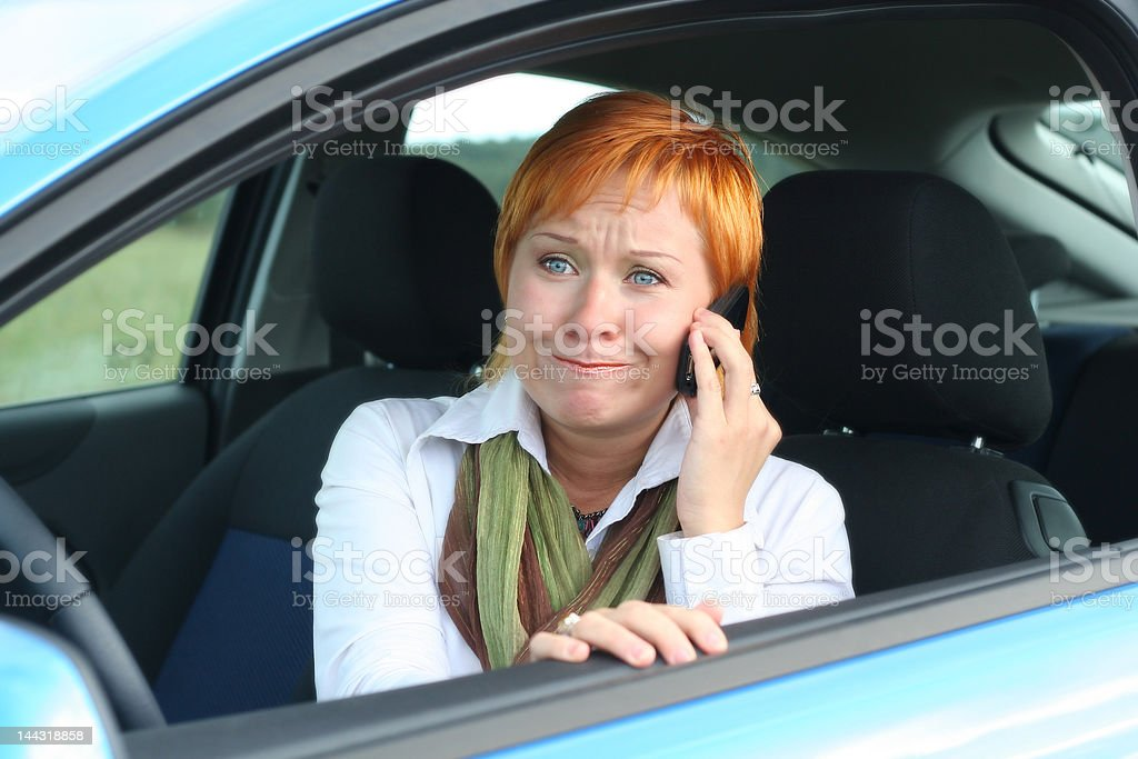 Red-haired woman with mobile-phone in a car royalty-free stock photo