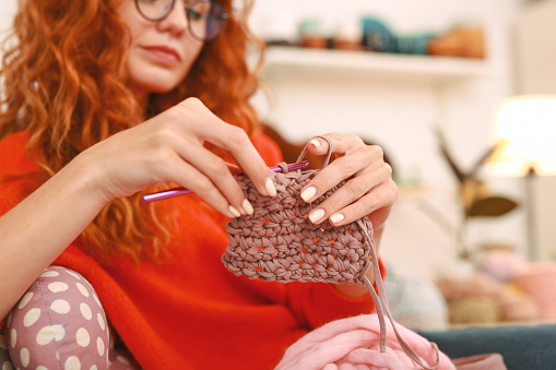 Red-haired woman with wavy hair knitting beautiful baby socks