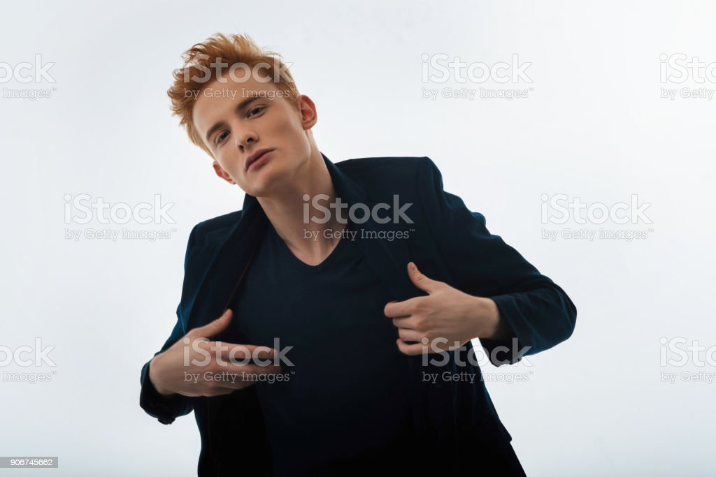 Red-haired young man putting on his jacket stock photo