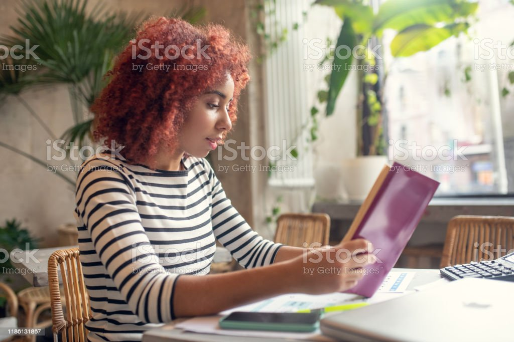 Red-haired young pretty businesswoman reading business literature - Royalty-free Adult Stock Photo