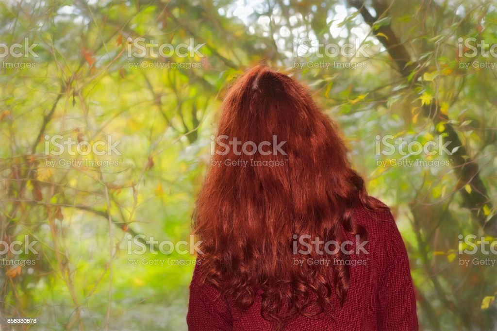Redhead autumn outdoor girl facing the season of falling leaves stock photo