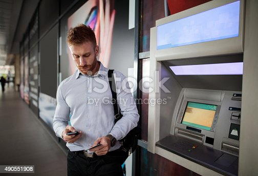 istock Redhead businessman using cell phone and credit card outdoors. 490551908