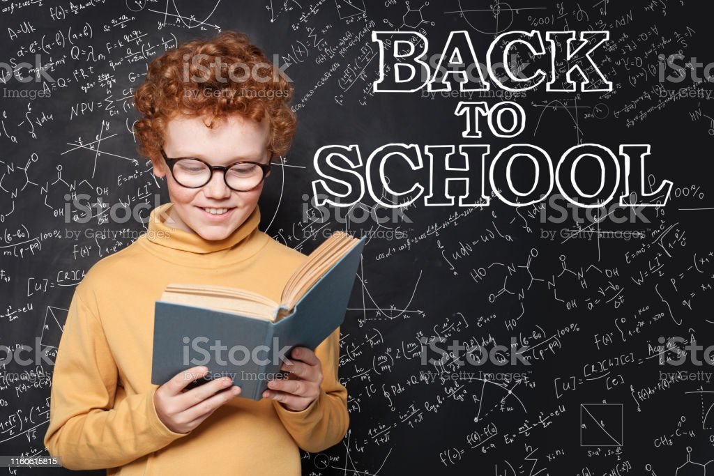 Redhead child reading a textbook on chalkboard background