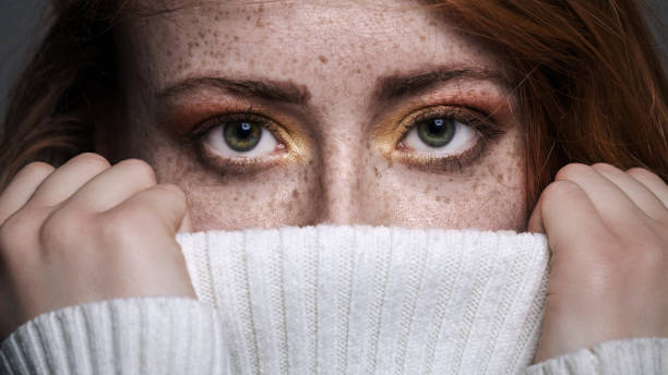 Redhead freckled woman looking out of sweater stock photo