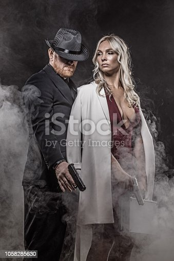 Redhead Gangster Mafia Man wearing hat and holding guns with a sexy blond bombshell woman in studio shoot