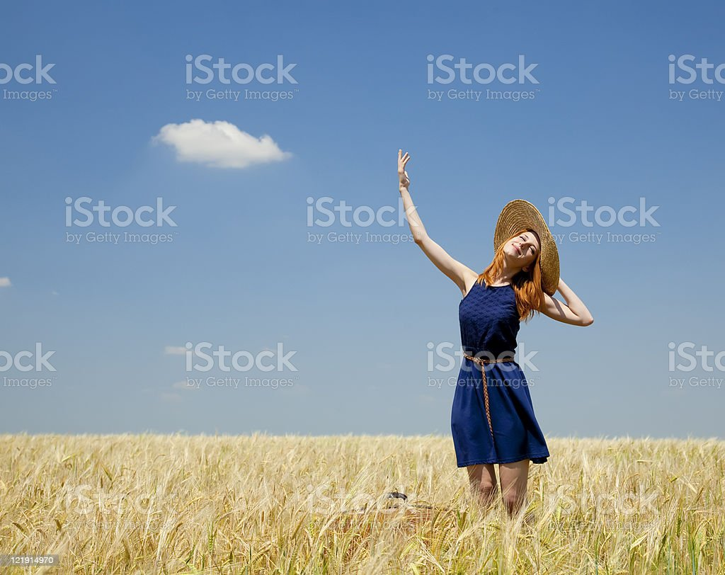 Redhead girl at spring wheat field royalty-free stock photo