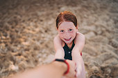 Portrait of redhead girl at the beach pulls his father's arm