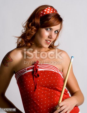 Redhead holding a pool cue stick, wearing a red polka dot outfit with. White background