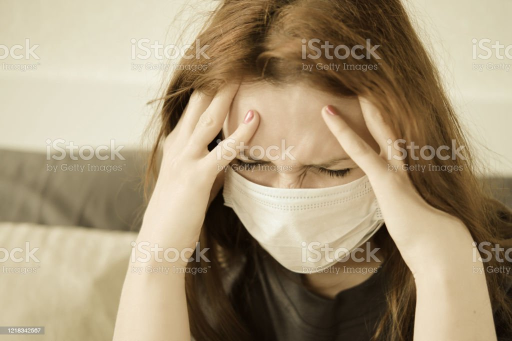 A redhead girl in a medical mask has a headache. Woman with a sore head sits on the bed A redhead girl in a medical mask has a headache. Woman with a sore head sits on the bed Adult Stock Photo