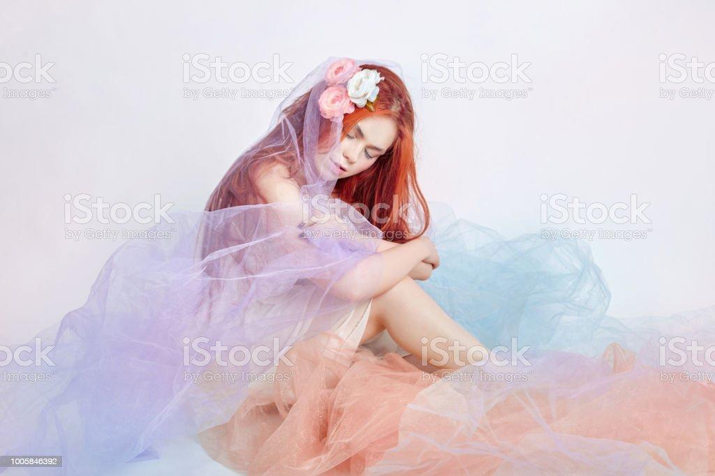 d3088072a8ad Ruiva em vestido colorido arejado claro senta-se sobre o fundo branco do  chão.
