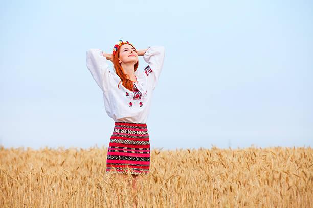 Capelli rossi ragazza in abito nazionale dell'Ucraina sul campo di grano. - foto stock