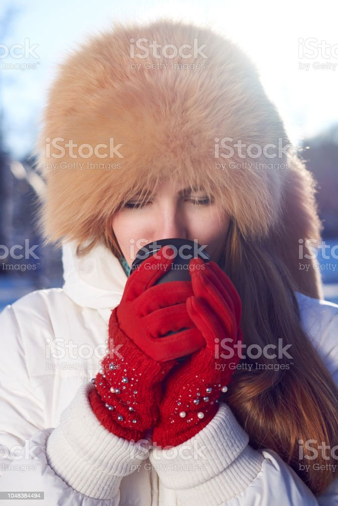 25e82fb5f745e Redhead girl, weared in fox fur hat and white jacket, drinking coffee to go  in winter cold day. - Stock image .
