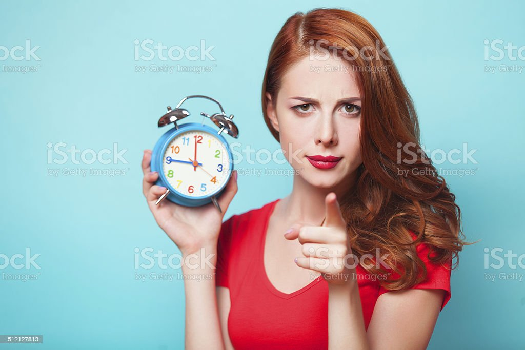 Redhead girl with alarm clock on blue background. stock photo