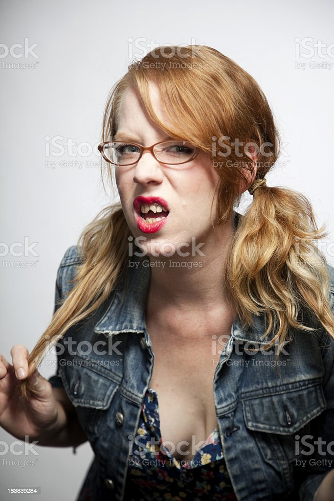 Redhead girl with glasses and bad teeth making a face. stock photo
