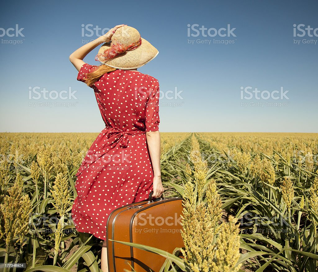 Redhead girl with suitcase at corn field. royalty-free stock photo