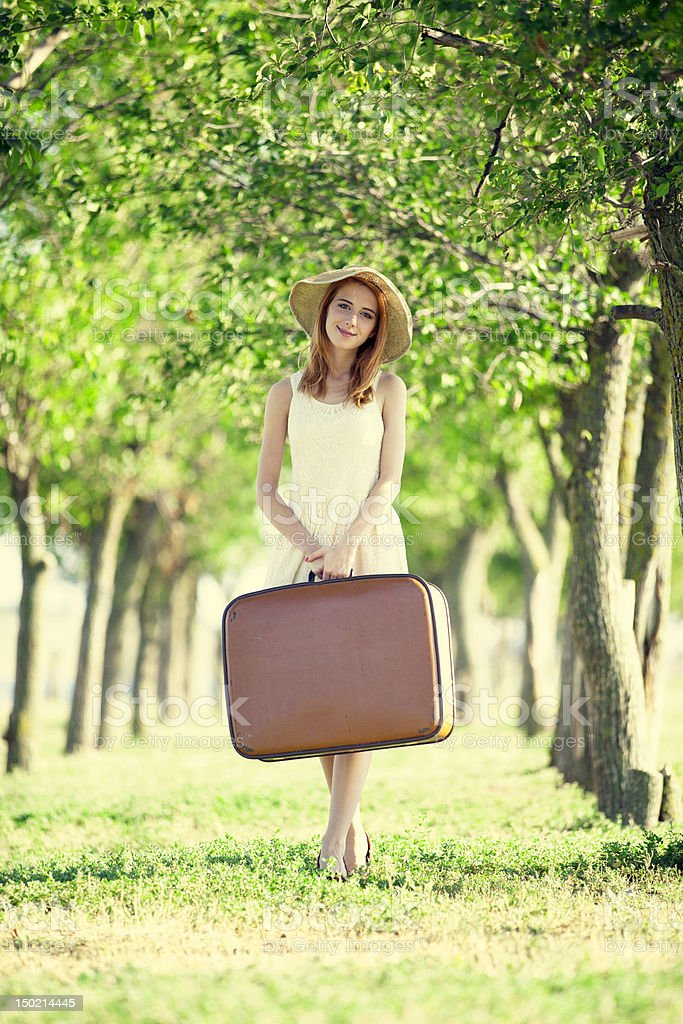 Redhead girl with suitcase at tree's alley. royalty-free stock photo