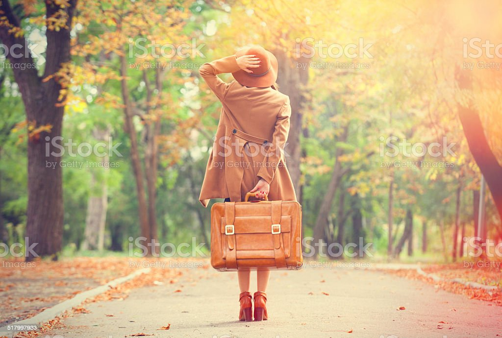 Redhead girl with suitcase in the autumn park. stock photo
