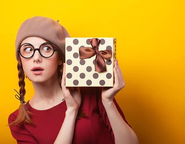rotes haar mädchen mit koffer auf gelbem hintergrund. - jugendliche geburtstag geschenke stock-fotos und bilder