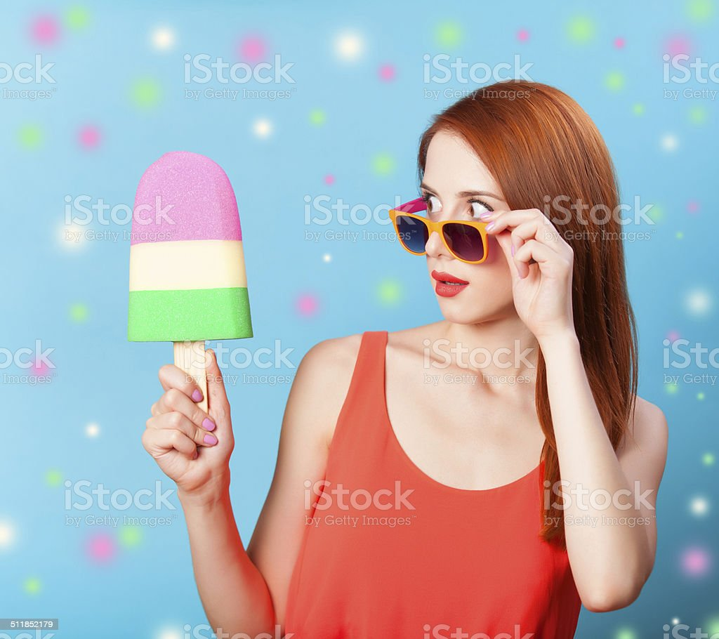 Redhead girl with toy ice cream on blue background. stock photo