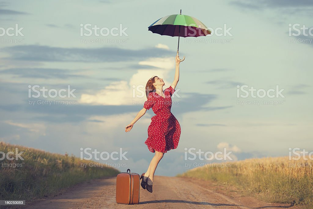 Redhead girl with umbrella and suitcase at outdoor stock photo