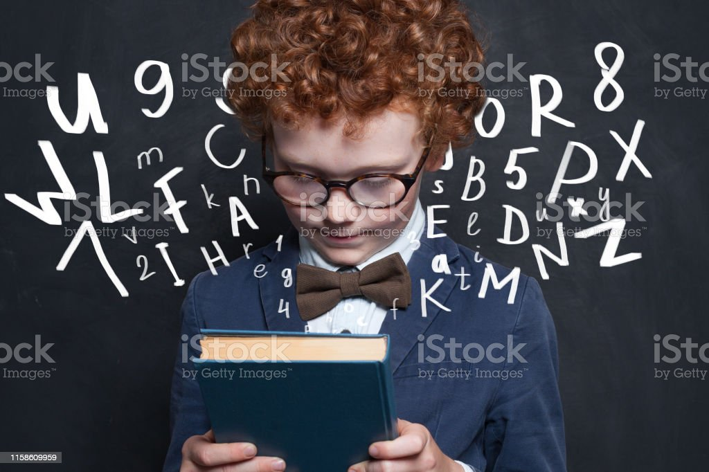 Redhead kid with book on school chalkboard background
