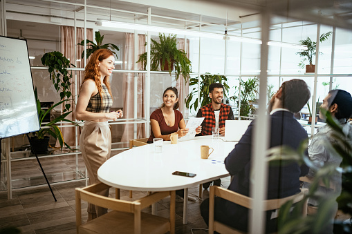 Latin businesswoman in office with colleagues, having presentation of business results