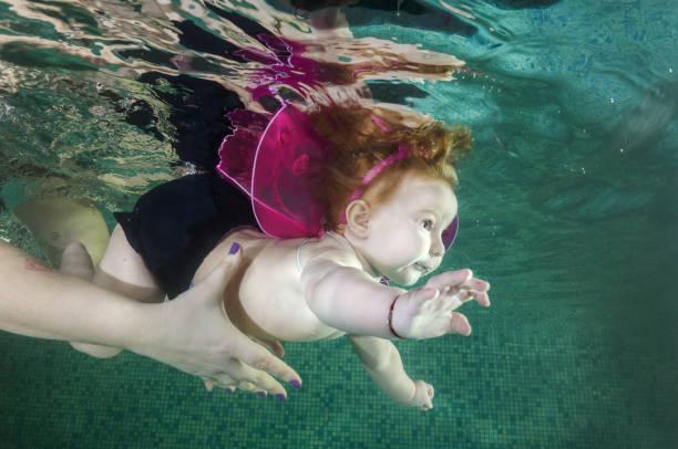 Redhead little girl  in elf costume swim underwater in the pool stock photo