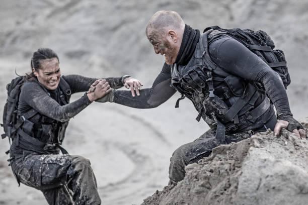 rothaarige männliche und brünette weiblichen militärangehörigen hart trainiert und einander auf einem sandhügel laufen - einen gefallen tun stock-fotos und bilder