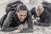 istock Redhead male and brunette female military swat security anti terror duo crawling  together during operations in muddy sand 902651248