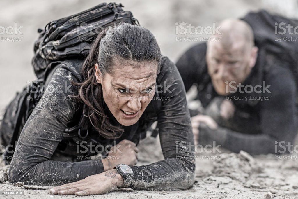 Redhead male and brunette female military swat security anti terror duo crawling  together during operations in muddy sand stock photo
