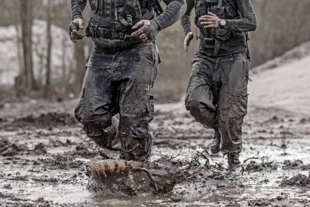 rothaarige männer und brünette weibliche militär swat sicherheit anti-terror-duo bei einsätzen im schlammigen im freieneinstellung - militärisches training stock-fotos und bilder